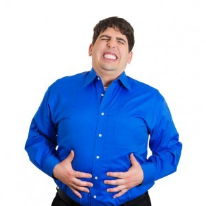 Man suffering from heartburn holds his stomach