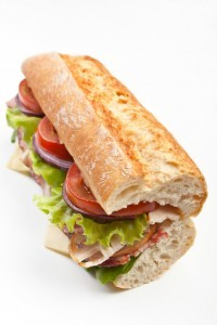 half of long tasty sub sandwich with lettuce, tomatoes, ham, turkey breast, salami and cheese