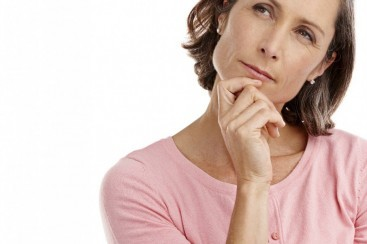 Mature thoughtful woman in pink shirt to represent breast cancer awareness