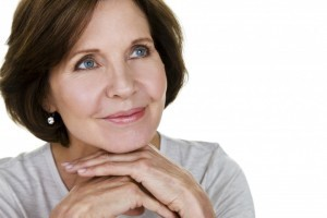 Attractive smiling older lady portrait chin on hands looking into distance