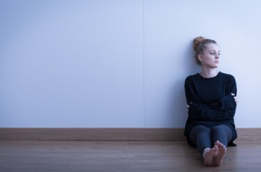 Depressed young woman sitting alone