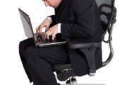 Man in desk chair with poor posture leading to back pain