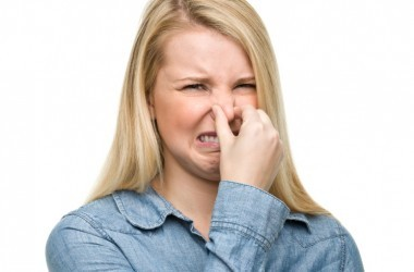 Woman holds nose because of a bad smell