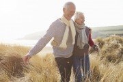 Happy older couple strolls outside through field