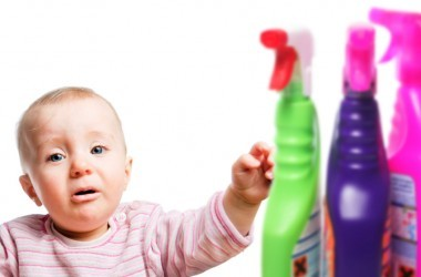 Crying baby pictured with cleaning chemicals