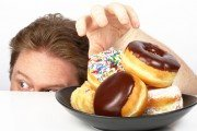 Hand sneakily reaching for a mood killing fat triggering doughnut