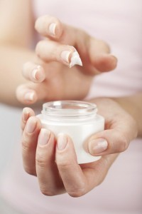 Close up of hands holding a small pot of some kind of skin cream