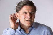 Man suffering from hearing loss deafness puts hand up to ear in danger of cognitive decline