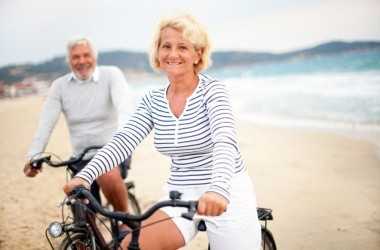 Happy older couple ride bikes ont he beach