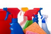 Tops of a variety of spray cleaner bottles with homemade essential oil cleaners inside