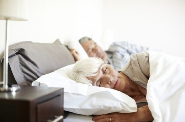 Senior woman sleeping in bed husband in background