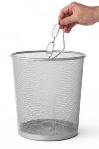 Man throws glasses in the trash can, isolated on white.