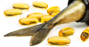 Tail of a raw fish with fish oil capsules laying next to it