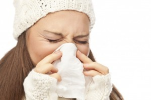 Woman  with flu blows her nose