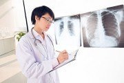 Doctor stands in front of chest x-ray medical imaging tests results