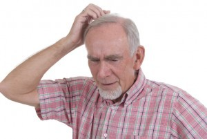 Confused man scratching head experiencing brain fog, a senior moment or memory loss