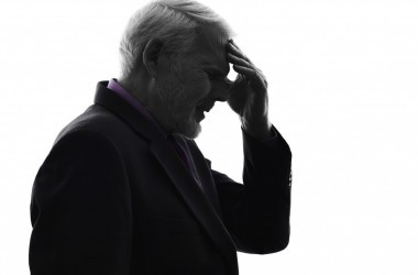 Older man in shadow holding head representing memory loss