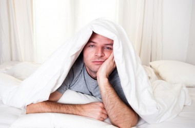 man in bed not getting enough sleep with insomnia and sleep disorder
