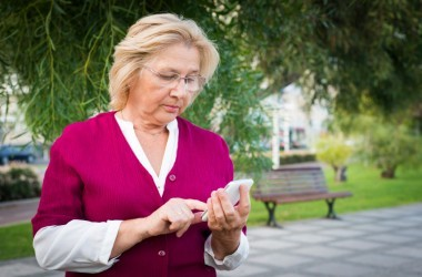 Mature woman dials cell phone