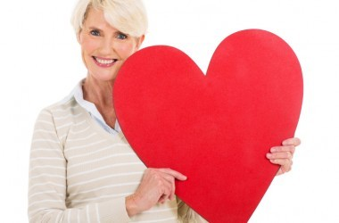 portrait of senior woman with heart shape against white background
