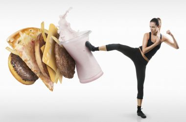 Woman kicking a stack of ultraprocessed food junk foods with food additives