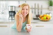 "Woman eating probiotic yogurt wondering ""How can I avoid a yeast infection?"""