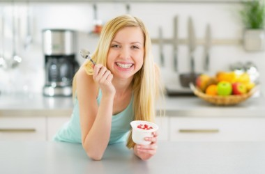 """Woman eating probiotic yogurt wondering """"How can I avoid a yeast infection?"""""""