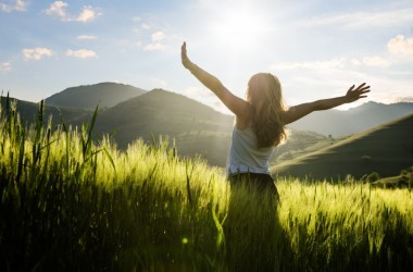 Woman standing arms stretched out to the sun getting vitamin D3 not vitamin D2