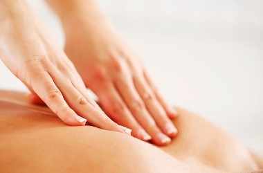 Close up of two hands massaging back to illustrate massage benefits such as pain relief