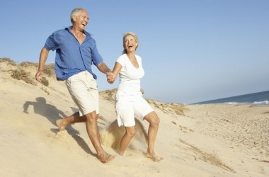 Happy older couple holding hands running on beach