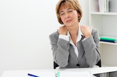 Mature woman having neck pain and back pain sitting at a desk