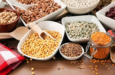Variety of legumes, heart disease superfoods, in bowls on table