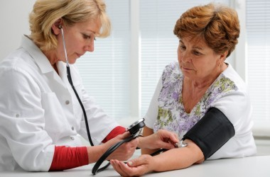 Doctor taking blood pressure reading on a woman