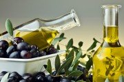 Glass bottles of olive oil and black olives in a bowl.