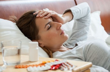 Woman sick with the flu lying in bed with drugs on nightstand.