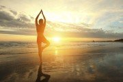 Woman doing yoga pose in front of lake at sunrise