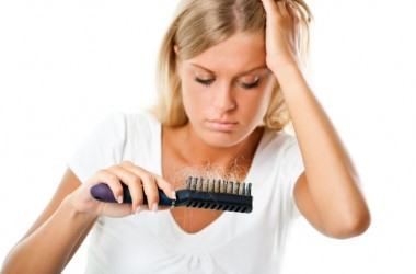Young woman looks at hairbrush with hair she lost in it