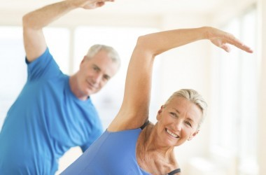 Fit seniors exercising in blue shirts
