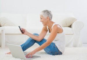 Sexy senior sits on the floor in front of a laptop and is texting on phone