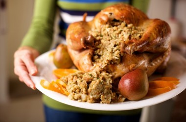 Woman holding turkey with trimmings on platter for traditional Thanksgiving menu