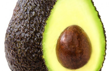 Bright green avocado with avocado seed on white background