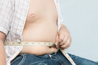 Guy using a measuring tape to measure his big belly gray background