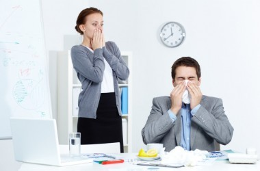 Image of man sneezing while a woman looks at him in fright afraid of cold and flu