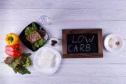 "Illustration of lower carbs foods on table with a small chalkboard with words ""low carb"" written on it"
