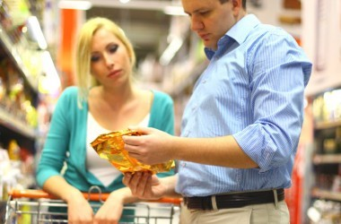 Couple reading food labels in the grocery store.