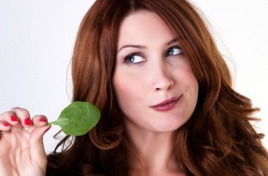 woman with a single spinach leaf to lower high blood pressure