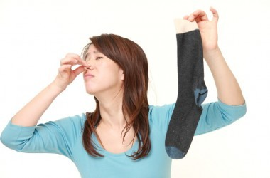 Woman trying to not smell stinky sock from foot odor, stinky feet smelly feet