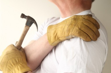 Man in pain with shoulder bursitis trying to use hammer
