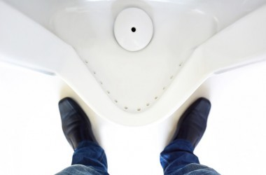 Many with prostate symptoms and prostate problems stands in front of a urinal.