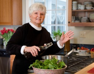 Mature woman sautes vegetables in olive oil